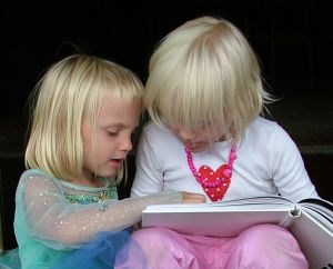 The image shows two young, pretty, blonde-haired little girls sitting close together, with a book on their knees which they are reading together.